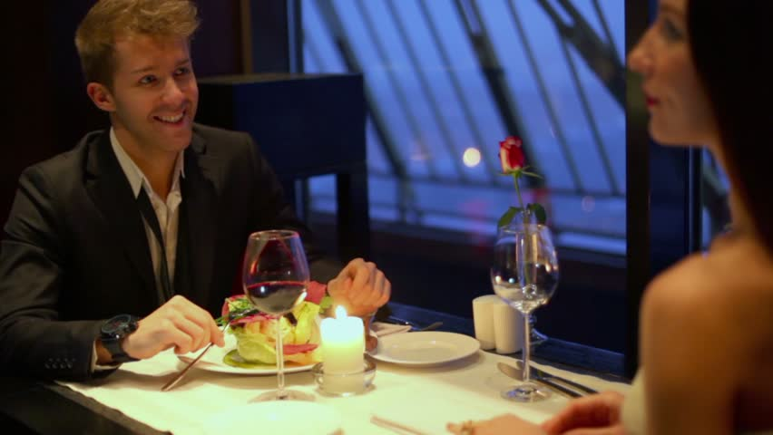 Waiter brings meal for brunette girl which sits at table with young guy - HD stock video clip