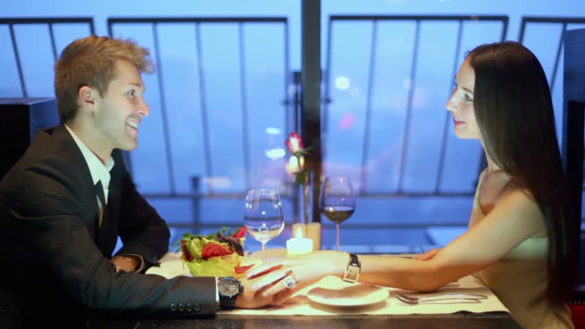 Lady in white dress touches hand of blond man during talk in restaurant - HD stock footage clip