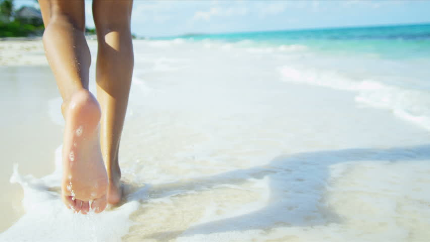 Bare legs feet young Latin American girl walking by ocean shallows shot on RED EPIC