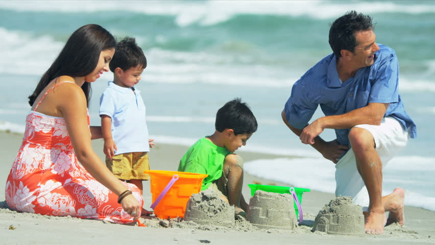 Happy Latin American parents enjoying summer time with little children by ocean shot on RED EPIC - HD stock video clip