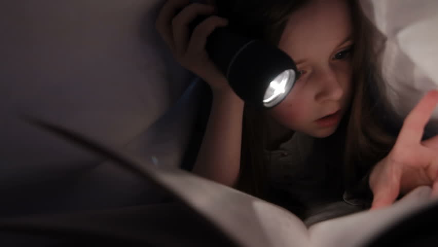 Child reading in bed - Little girl reading by torch light under the bed sheets - HD stock footage clip