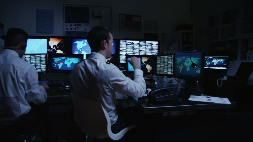 A team of male security personnel working in a busy system control room, could be a weather station/airport traffic control. It could be a  power station or police/army control facility. Slow motion.