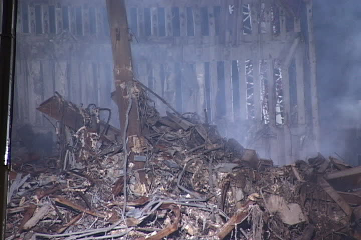 NEW YORK CITY - SEPTEMBER 28, 2001: Pile of rubble with smoke rising in front of remains of World Trade Center structure.