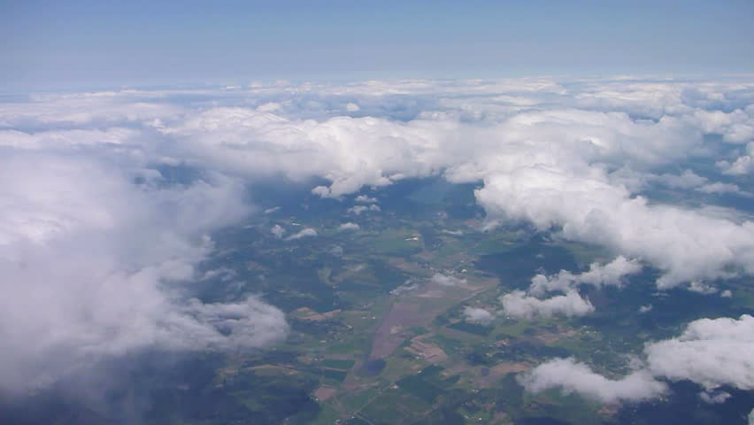 Flying in airplane over pacific northwest with clouds below and blue