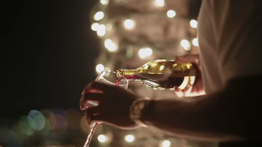 Man pouring wine into glasses at a party - HD stock footage clip