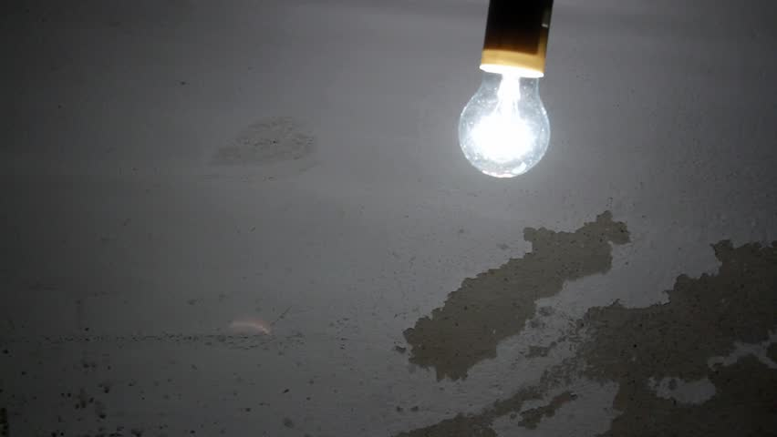 Loop-able swinging light bulb on peeling concrete wall