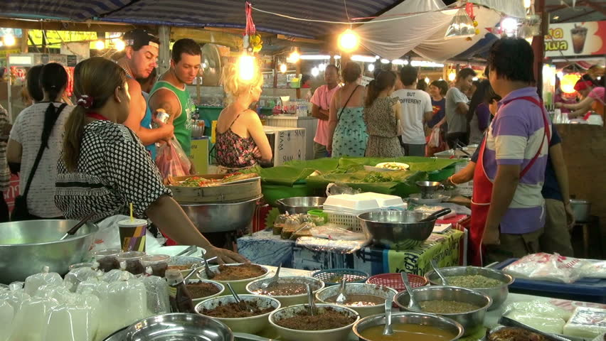 PHUKET, THAILAND - 11 MAY 2013 - Street food market in Phuket, Thailand. People pass trough food vendors and tourists look at the food stall.