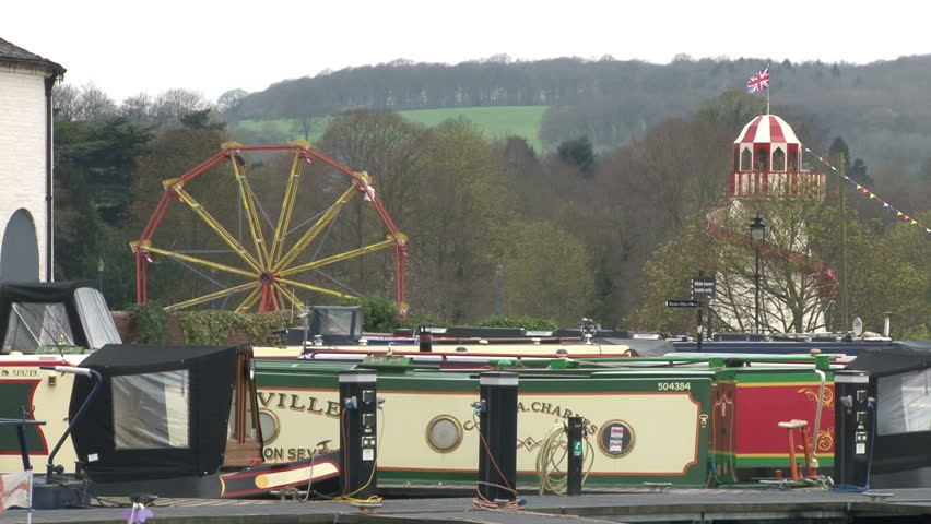 WORCESTERSHIRE, UK - CIRCA 2012:Amusement park situated next to moored canal boats. - HD stock video clip