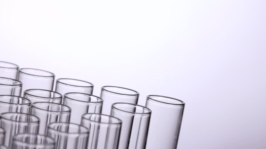 A pipette drips blue chemicals into a test tube - HD stock video clip