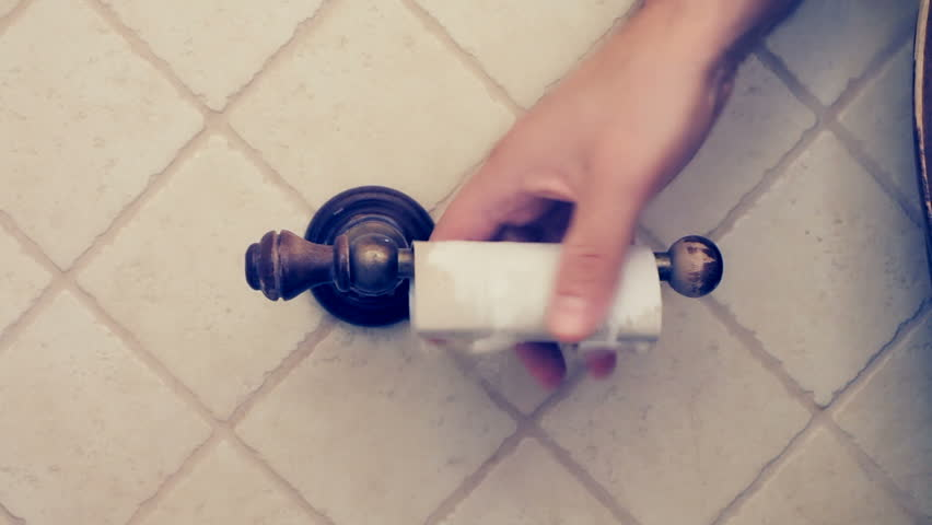 A man sits down on a toilet seat in a bathroom, he grabs the toilet paper roll and he discovers it's ended.