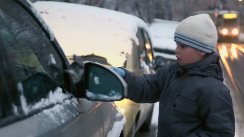 Young boy cleans car from snow at street with tram rides at evening