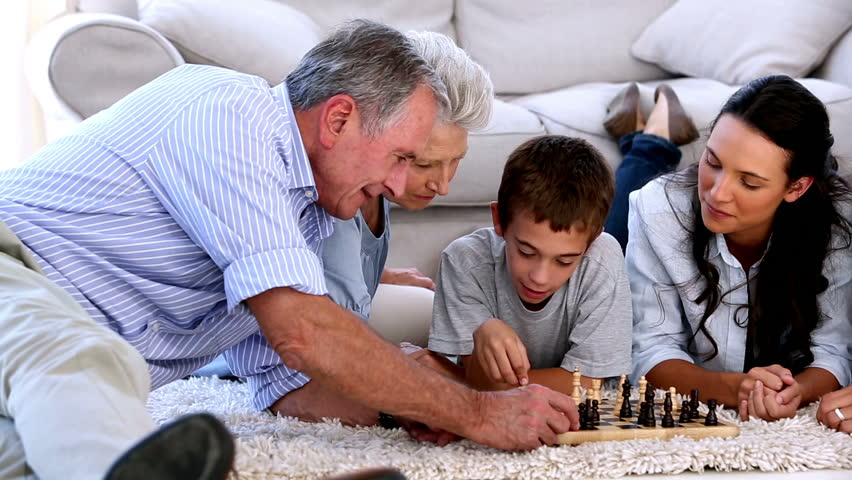 Extended family playing chess together on the floor at home - HD stock footage clip