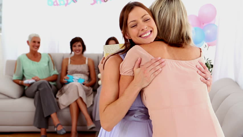 Pregnant woman receiving hugging her friend and getting a present at her baby shower at home