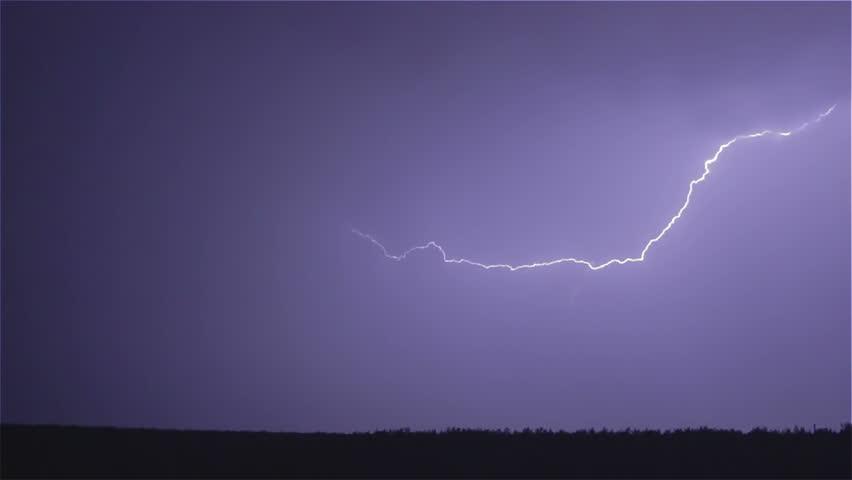 Various lightning bolts strike forest night landscape, sound included