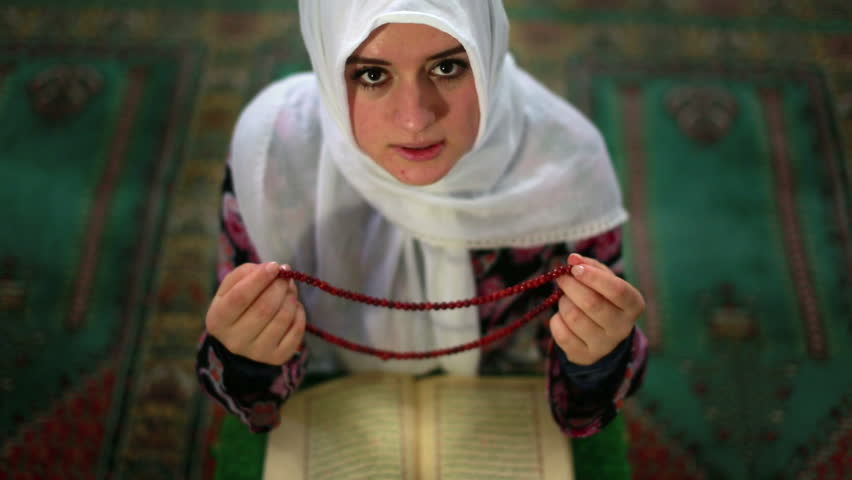 Muslim girl saying her everyday salat prayer, using prayer beads