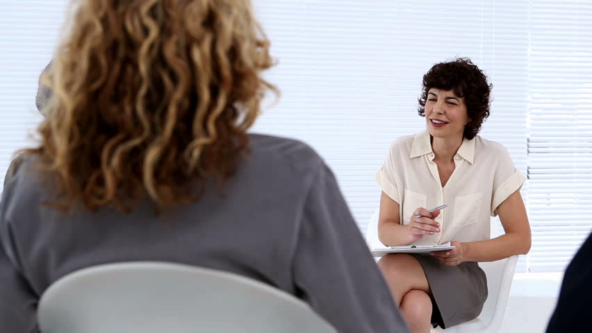 Woman therapist listening to her group of patients