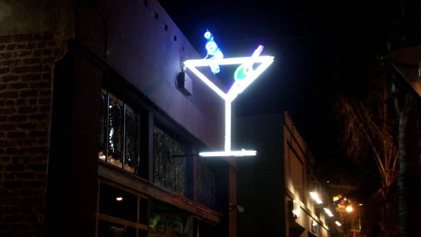 Shot of a neon martini glass sign on a tavern at night. Features a bright green olive and blinking blue bubbles.