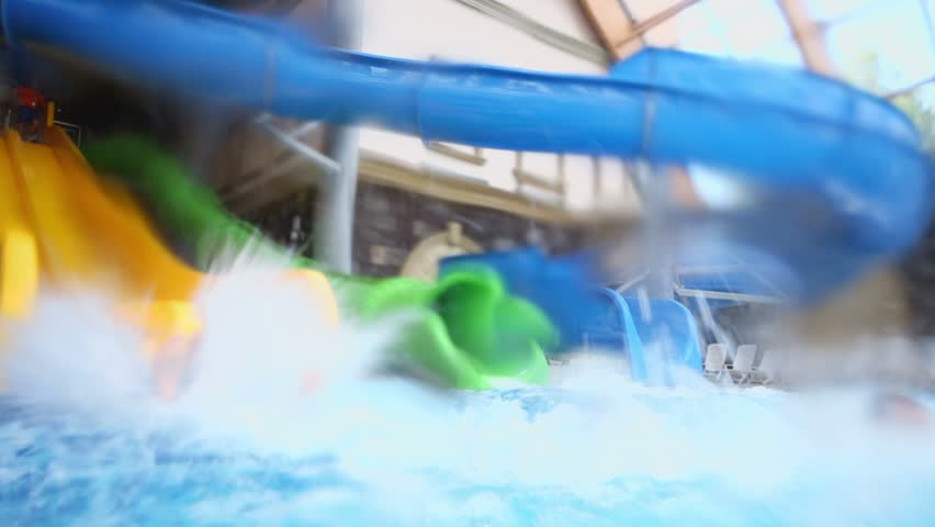 Two kids slid from big colorful water slides in pool at indoor aqua park. - HD stock video clip