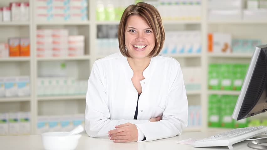 Young Female Pharmacist With Customer At Pharmacy Stock