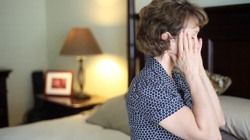 A troubled, stressed out woman sitting on her bed who appears to be suffering from a headache - HD stock footage clip