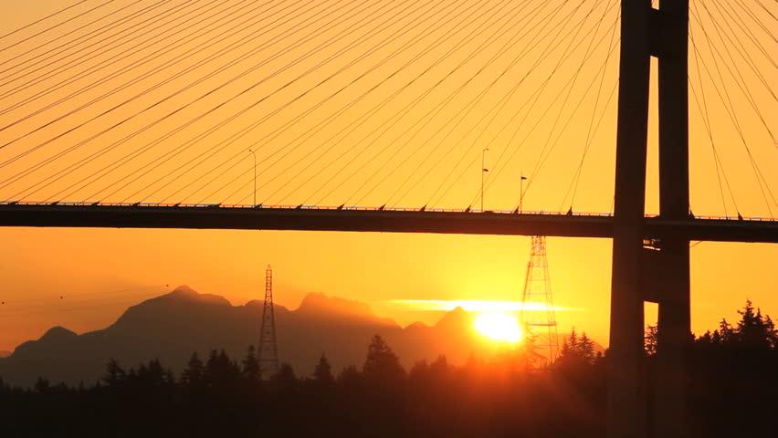 Morning Bridge Sunrise Commuter Traffic. The Alex Fraser Bridge at sunrise spanning the Fraser River at Delta, BC near Vancouver. Canada.  - HD stock video clip