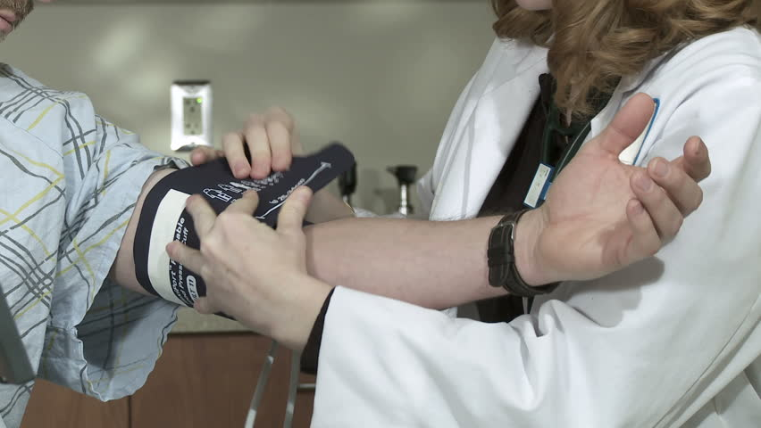 Close up of female doctor taking the blood pressure of a mature male patient. - HD stock video clip