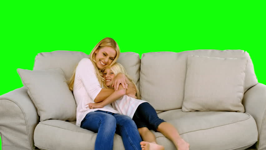 Daughter jumping in the arms of her mother in the sofa on green screen in slow motion - HD stock video clip