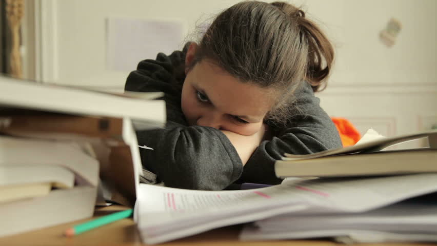 Female student looking tired of studies. Around her are piles of books and papers