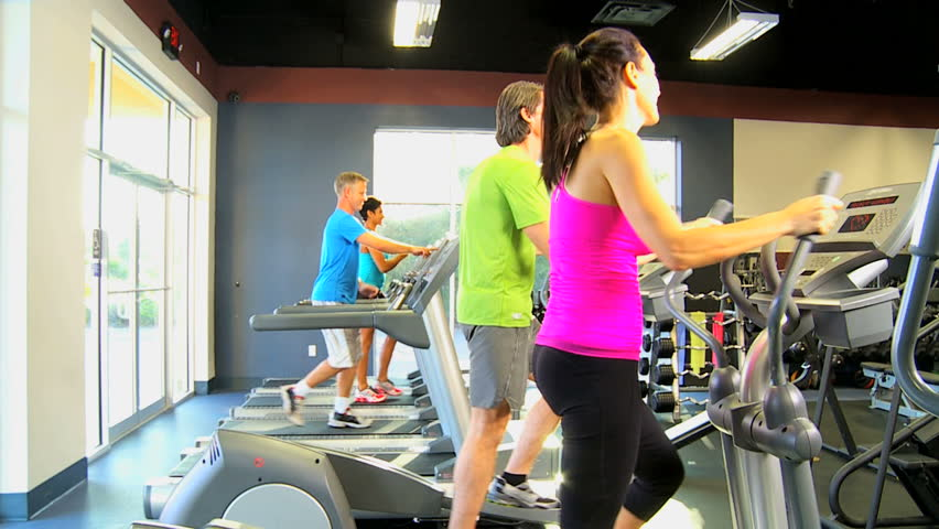 Multi ethnic gym members exercising on modern cross walkers and treadmills as part of healthy lifestyle