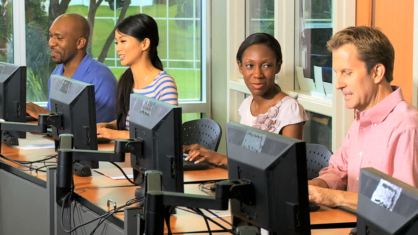 Close up mature students attending college IT course using modern technology