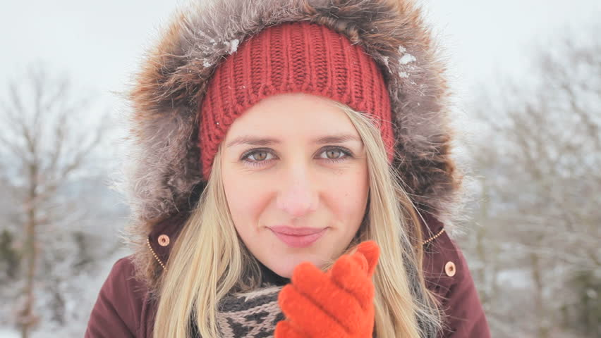 Close up portrait pretty blonde girl wrapped in warm winter clothing blowing on gloved hands to keep warm