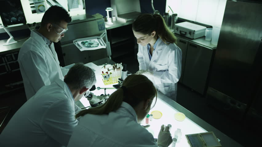 A mature male scientist or medical researcher is working in a dark laboratory, teaching a young team of students or trainees.