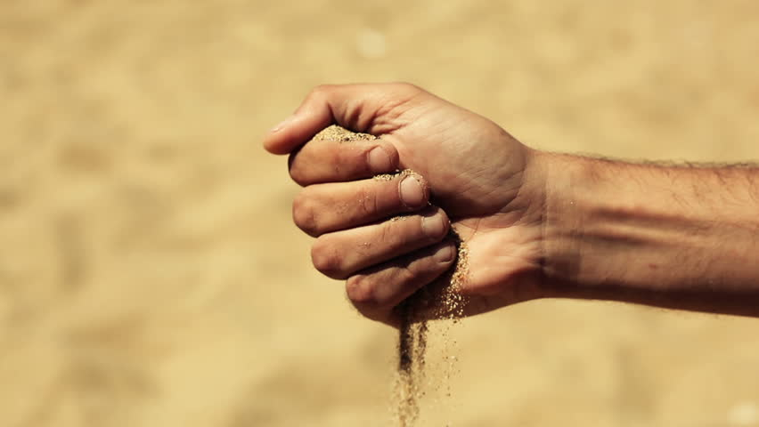 sand in the hands of men