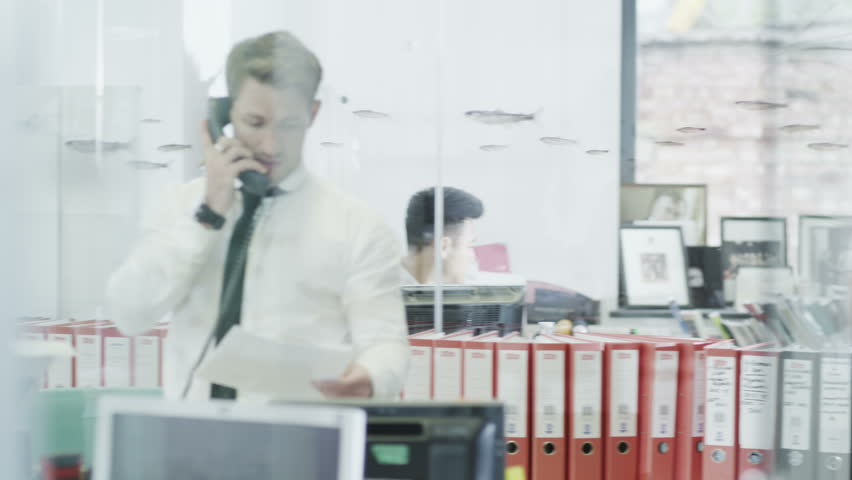Confident young businessman takes a call in an informal but busy modern office. In slow motion.