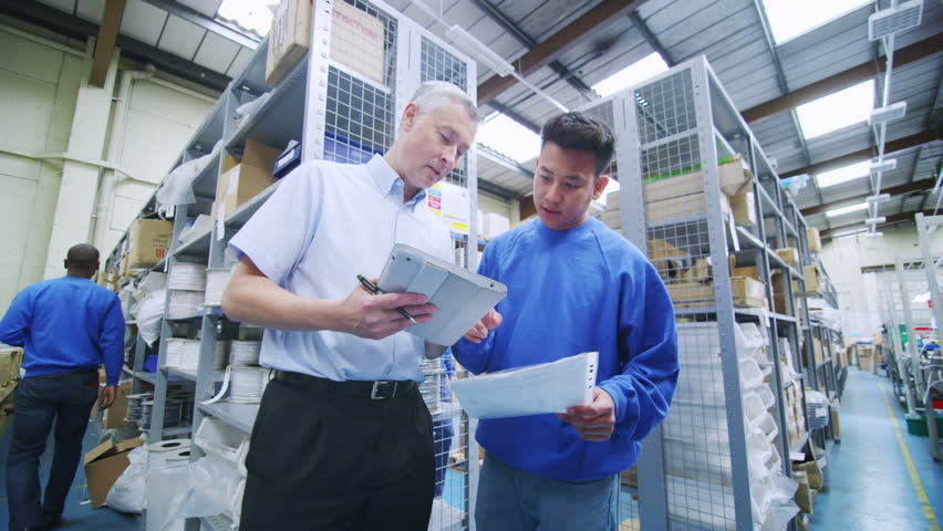 Young asian factory or warehouse worker taking instruction from the foreman or manager. The rest of the company staff can be seen working in the background.