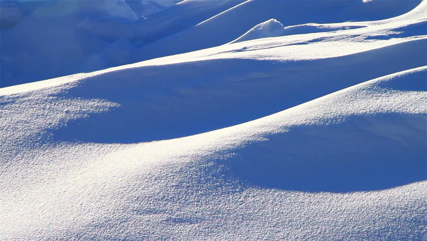 Snowy forms of winter backlit by sunlight, panning shot, closeup