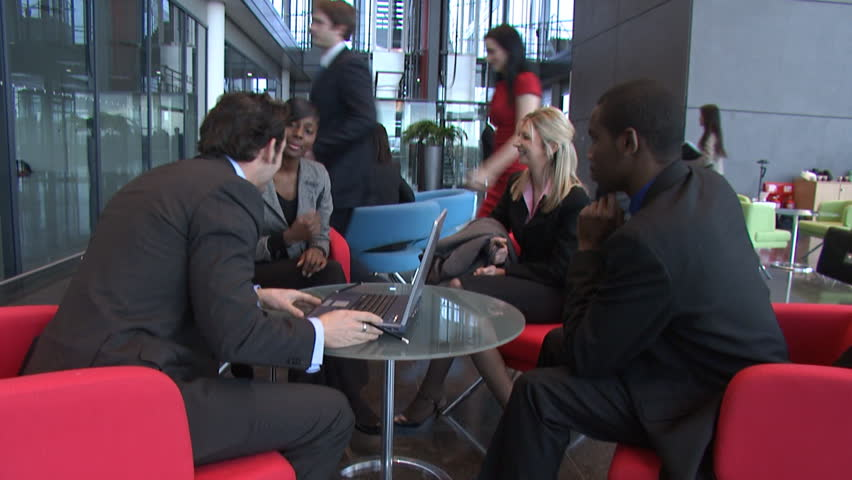 Large multi ethnic business group in relaxed meeting area of a large financial corporation building. High quality HD video footage