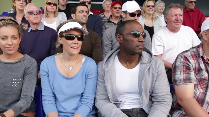 Enthusiastic crowd of tennis sports fan spectators. People young and old cheering and smiling.