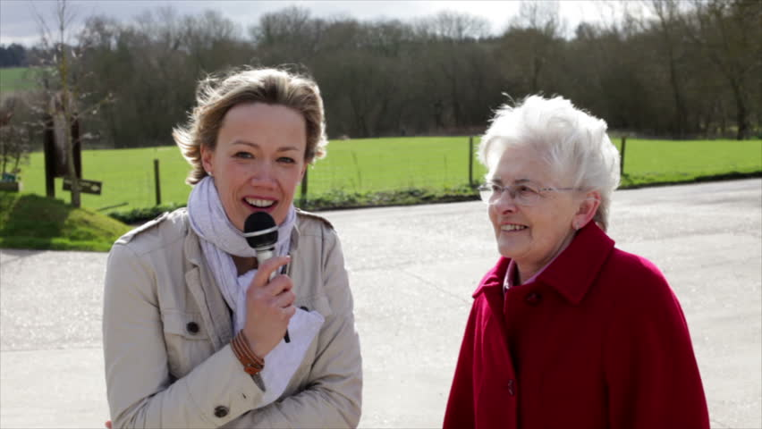 News reporter on location interviewing senior lady outdoors