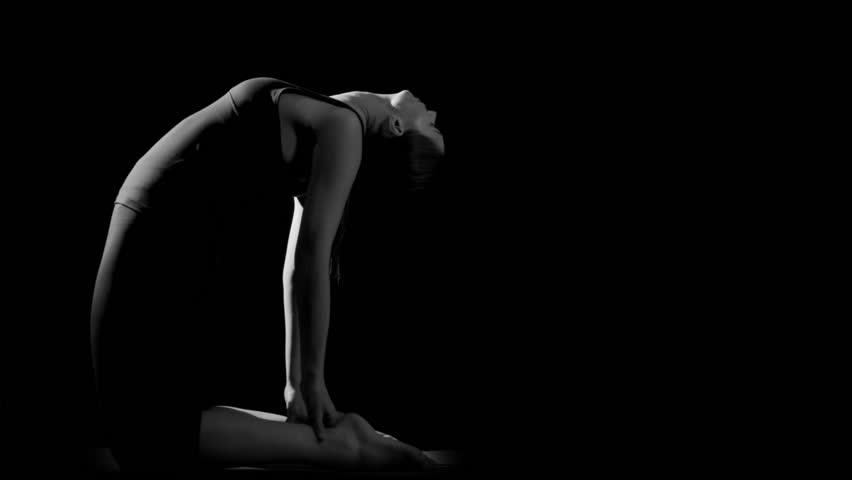 Flexible gymnast stretching backwards against black background. Black and white. Slow motion.