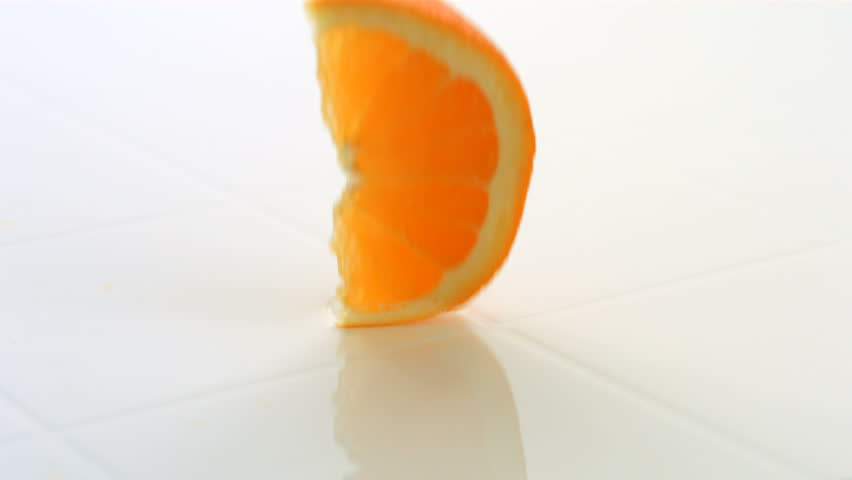 Orange slices splashing into water, slow motion
