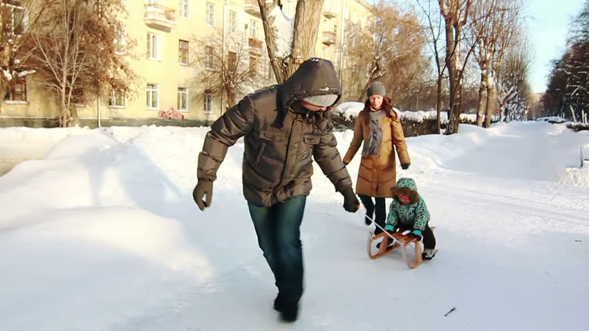 Father, who is pulling his son in sled. Park in winter.