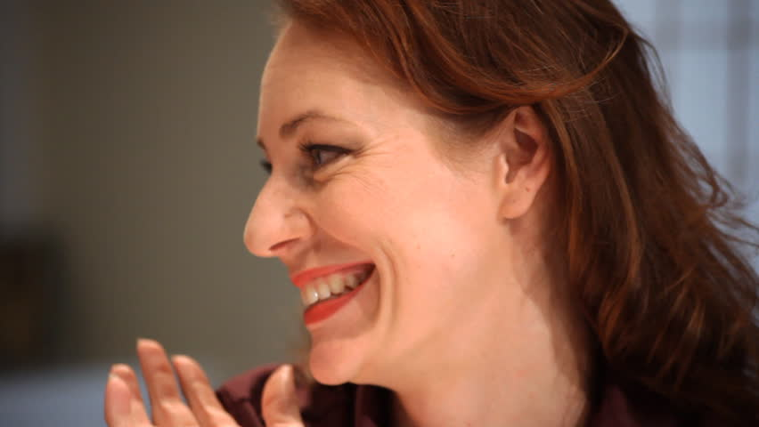 A pretty redhead with lovely blue eyes smiling and laughing. - HD stock footage clip