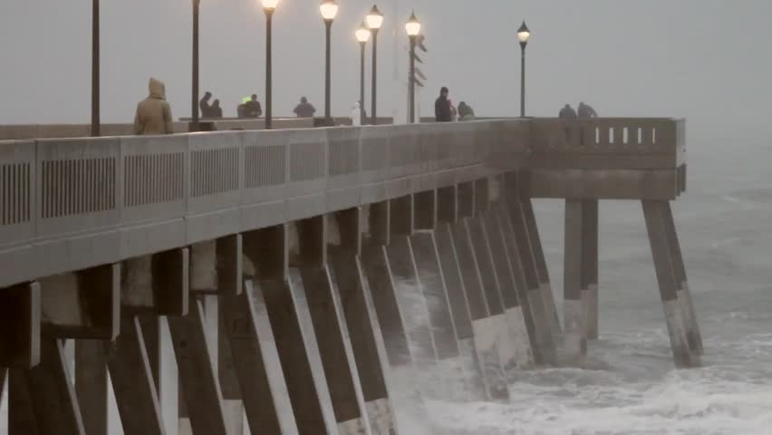 Footage from Hurricane Sandy as it passed by Wrightsville Beach, NC. Tension builds as wind and rain blow sideways.  Shots of pier with waves crashing. Sea foam, water sprays, waves pound beach. Edited Sequence.