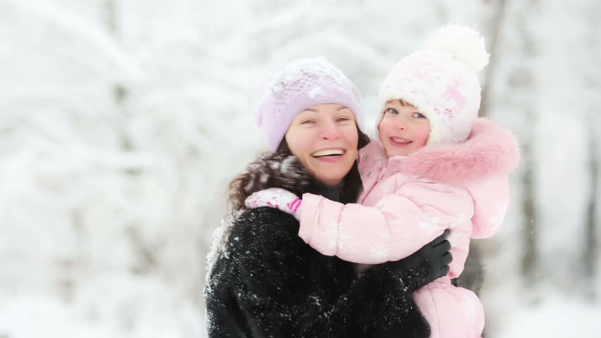 Happy woman and child playing with snow in winter park. Slow motion