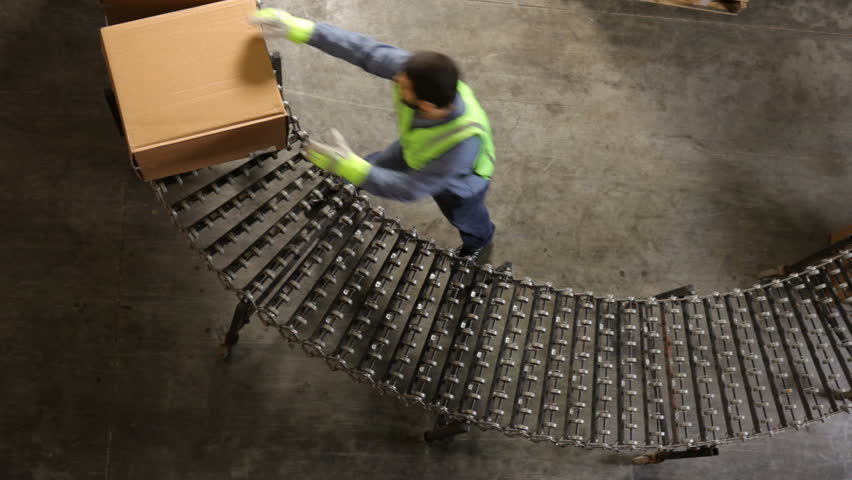 Man in shipping warehouse moves boxes along conveyor