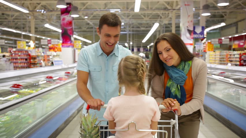 Smiling parents pushing a shopping trolley with their daughter sitting inside