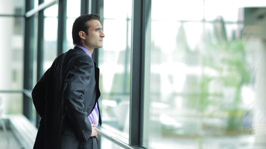 A businessman looks out the window in a contemplative way. Medium shot