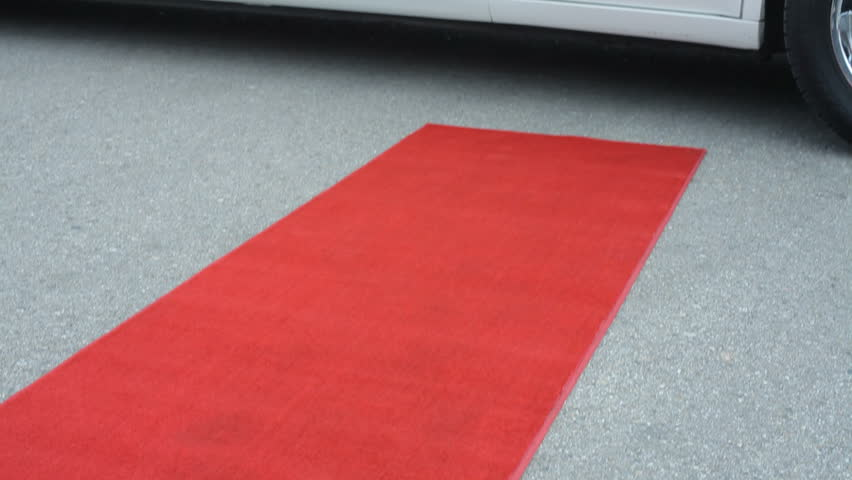 Businessman steps out of limo onto red carpet
