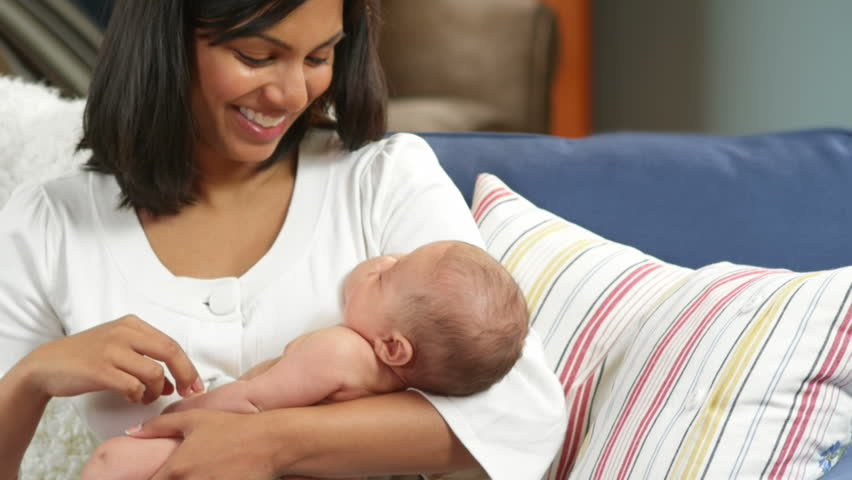 A newborn gets a slight tickle by his mother while she sleeps. Medium shot.
